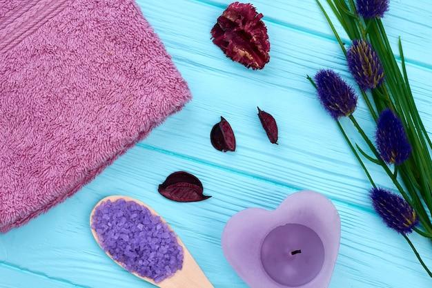 Arranjo plano de material de banheiro de spa em madeira azul. toalha roxa com vela e colher.