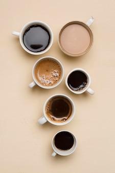 Arranjo plano de xícaras de café diferentes