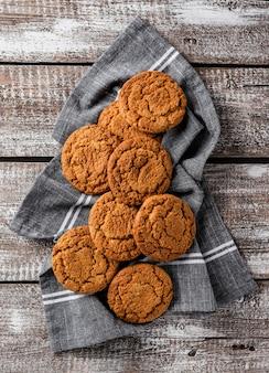 Arranjo plano leigo de biscoitos cozidos frescos em pano de cozinha
