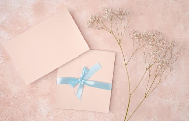 Arranjo rosa com convite de casamento
