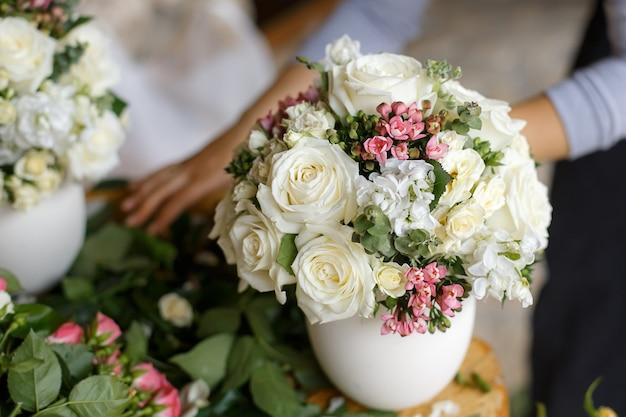 Arranjos de casamento com um mix de flores frescas em vasos brancos.