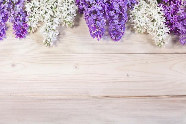 Arranjos de flores abstratos. uma moldura de ramos lilás em uma mesa de madeira.