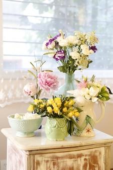 Arranjos de flores de rosas amarelas, peônias, jasmim em vasos de cerâmica originais