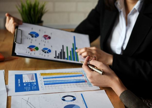 Arranque de conceitos de negócios, a equipe do novo escritório está analisando dados de gráficos.