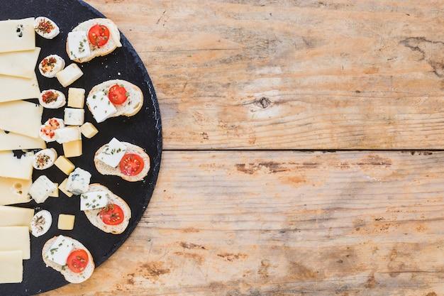 Arranque de queijo saboroso com pão na placa de ardósia preta na mesa de madeira