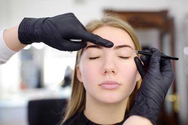 Arranque de sobrancelha cosmetologista. mulher atraente, recebendo cuidados faciais e maquiagem no salão de beleza. sobrancelhas de arquitetura.