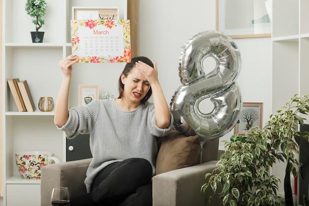 Arrependi de colocar a mão na testa linda garota no feliz dia da mulher segurando o calendário, sentado na poltrona na sala de estar