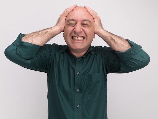 Arrependido com os olhos fechados, homem de meia-idade vestindo uma camiseta verde agarrada na cabeça isolada na parede branca