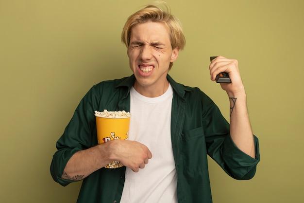 Arrependido com os olhos fechados, jovem loiro vestindo uma camiseta verde segurando um balde de pipoca e levantando o controle remoto da tv
