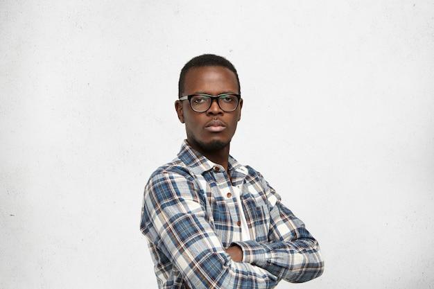 Arrogante jovem afro-americano hipster usando óculos de armação preta e camisa quadriculada, olhando com expressão facial pedregosa indiferente, mantendo os braços cruzados