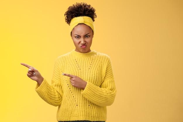 Arrogante peeky jovem namorada comportar-se rude desrespeitoso carrancudo enrugamento nariz nojo ofensa apontando para a esquerda carrancudo desgosto aversão ao aborrecimento, expressar decepção, fundo amarelo em pé.