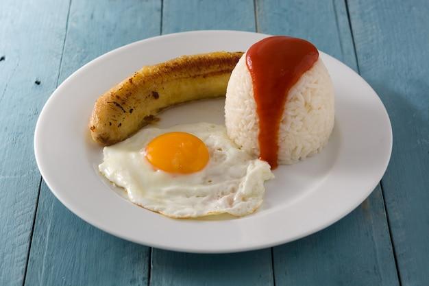 Arroz a la cubana arroz cubano típico com banana frita e ovo frito em um prato na mesa de madeira.