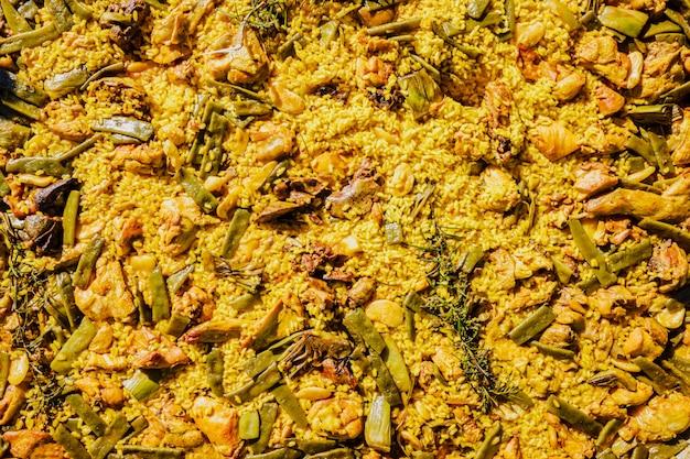 Arroz amarelo com carne e legumes na paella valenciana