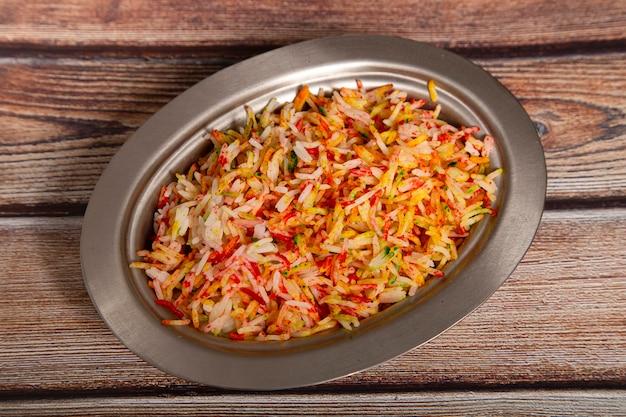 Arroz basmati com especiarias e vegetais isolados na vista superior da mesa de madeira. comida indiana