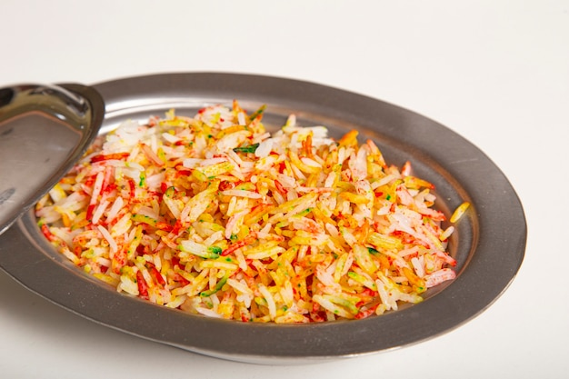 Arroz basmati cozido com especiarias e vegetais isolados na mesa branca comida vegetariana indiana.