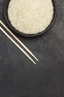 Arroz basmati em uma tigela preta. varas de bambu na mesa.