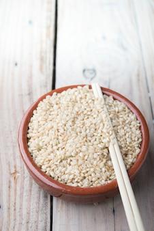Arroz basmati indiano, arroz basmati paquistanês, arroz basmati asiático, arroz basmati cozido, arroz branco cozido, arroz liso cozido em tigela de madeira sobre madeira marrom