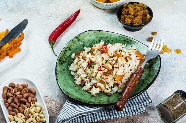 Arroz biryani e caril de comida indiana. comida do ramadã. arroz basmati. conceito de comida indiana. cozinha árabe. amendoim e pimenta. passas, damascos secos