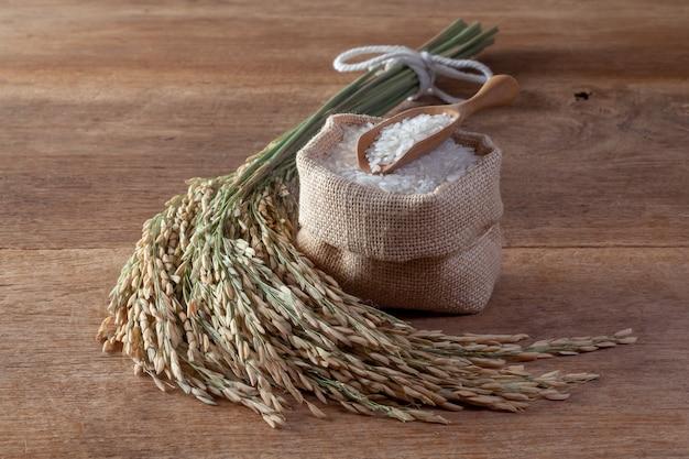 Arroz branco (arroz de jasmim) em um saco em um fundo de madeira