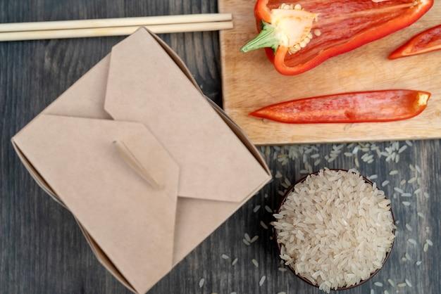 Arroz branco asiático com vegetais em uma caixa de papel.