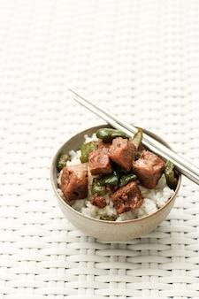 Arroz branco com bife saikoro pimenta preta e pimentão verde. servido em uma tigela como uma tigela de arroz