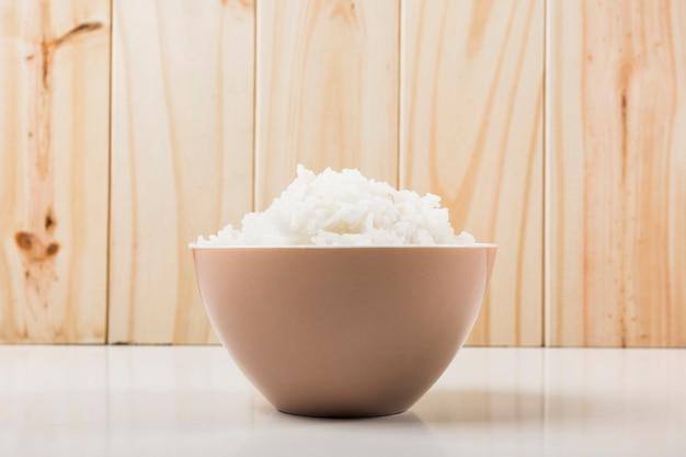 Arroz branco cozido na tigela na mesa branca contra o fundo de madeira