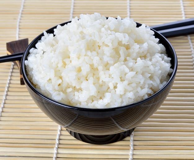 Arroz branco cozido no vapor em tigela redonda preta