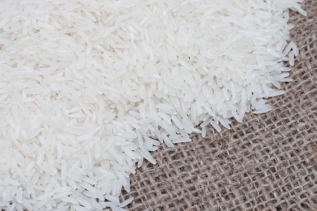 Arroz branco cru (arroz do jasmim) no saco marrom.