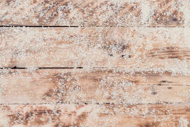 Arroz branco cru espalhado sobre a superfície de madeira texturizada