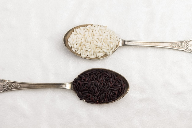Arroz branco e preto em colheres de metal. postura plana