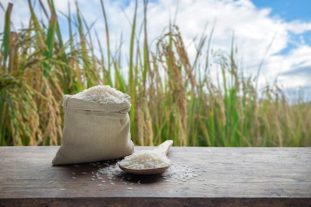 Arroz branco em saco e colher de pau com fundo de campo de arroz