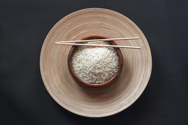 Arroz branco em tigela de madeira com pauzinhos de madeira