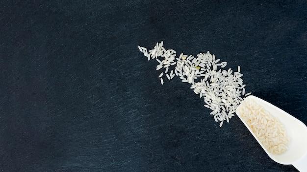 Arroz branco em uma colher na mesa preta
