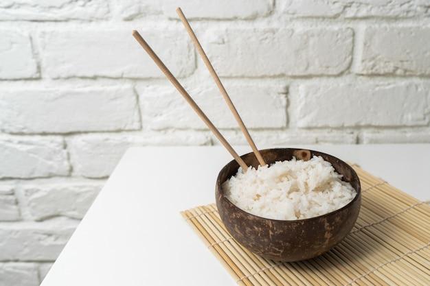 Arroz branco em uma tigela de coco em um fundo branco. foto minimalista com pauzinhos de arroz e bambu.