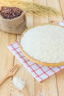 Arroz branco jasmim tailandês e arroz riceberry em cesta de bambu e saco em fundo de madeira