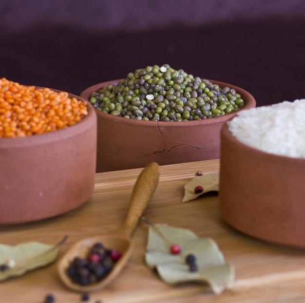 Arroz branco, lentilhas vermelhas e ervilhas verdes mache na bandeja de madeira. baía