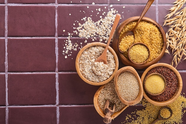 Arroz branco, marrom e vermelho, trigo sarraceno, painço, sêmolas de milho, quinua e bulgur em tigelas de madeira sobre uma mesa de cozinha de pedra marrom. cereais sem glúten. vista superior com copyspace