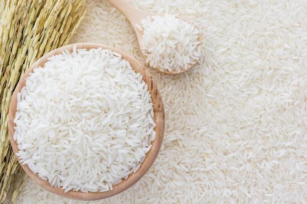 Arroz branco na tigela e um saco, uma colher de pau e planta de arroz em fundo de arroz branco