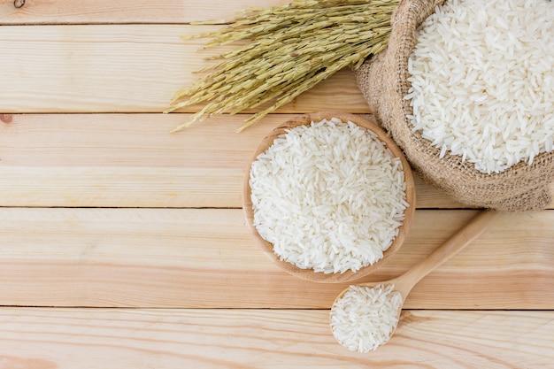 Arroz branco na tigela e um saco, uma colher de pau e planta de arroz em uma mesa de madeira