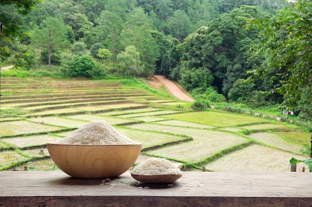 Arroz branco ou não cozido em uma tigela de madeira e colher de madeira arroz branco com o campo de arroz em terraços