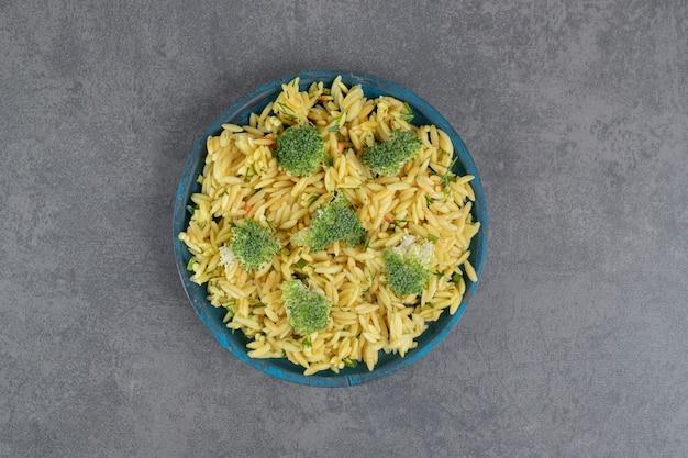 Arroz caseiro com brócolis na placa azul. foto de alta qualidade
