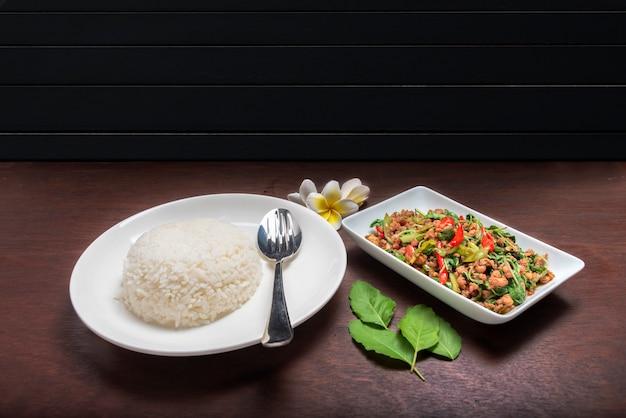 Arroz com carne de porco frita com folhas de manjericão em prato branco na mesa marrom escuro