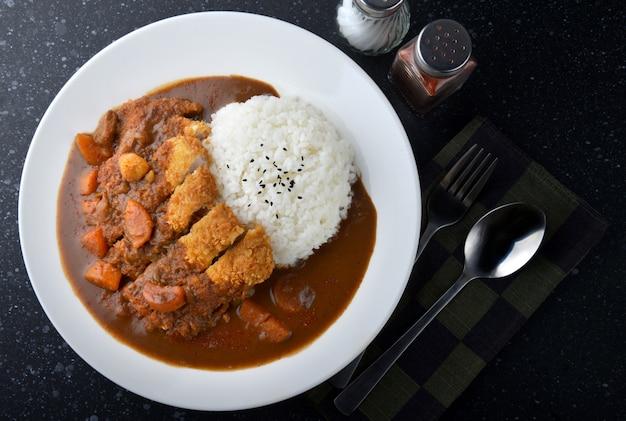 Arroz com carne de porco frita e curry.