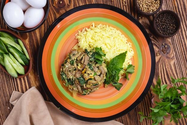 Arroz com carne espinafre ovos especiarias verdes vista superior