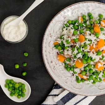 Arroz com feijão verde e cenoura no prato perto de molho na tigela