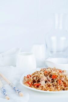 Arroz com legumes e frango em um fundo branco