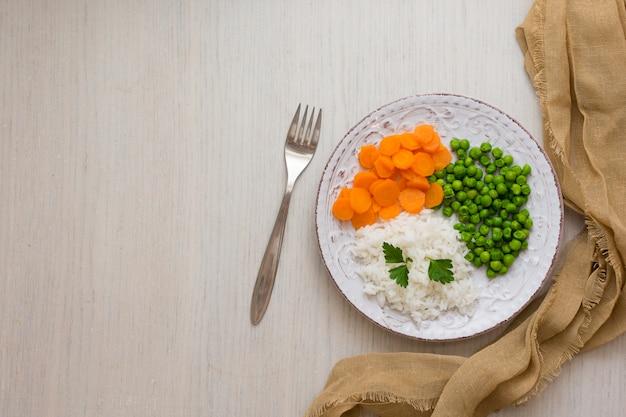 Arroz com legumes e salsa no prato com garfo