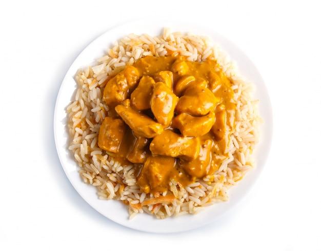 Arroz com molho de caril da galinha com o caju isolado na superfície branca.