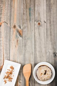 Arroz com molho de soja e canela na bandeja branca com espátula na mesa de madeira