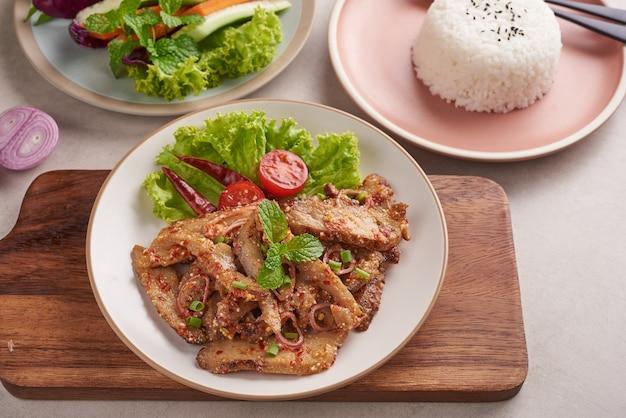 Arroz com pescoço de porco grelhado. salada de porco grelhada comida tailandesa com ingredientes de ervas e especiarias, comida tradicional nordestina deliciosa com vegetais frescos, fatia picante e picante em menu de carne de porco grelhada comida asiática.